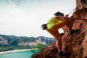 woman rock climber climbing on seaside cliff